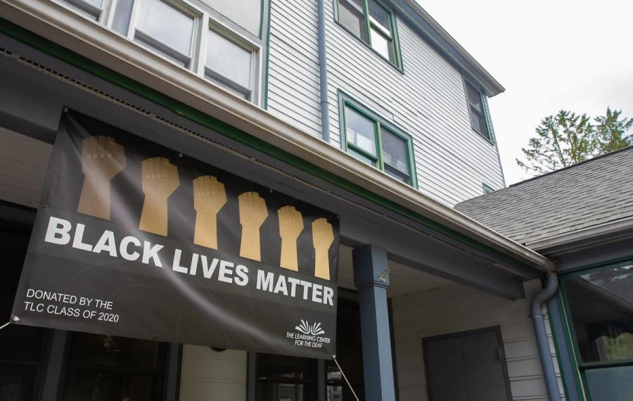 A banner hanging from a building reads Black Lives Matter