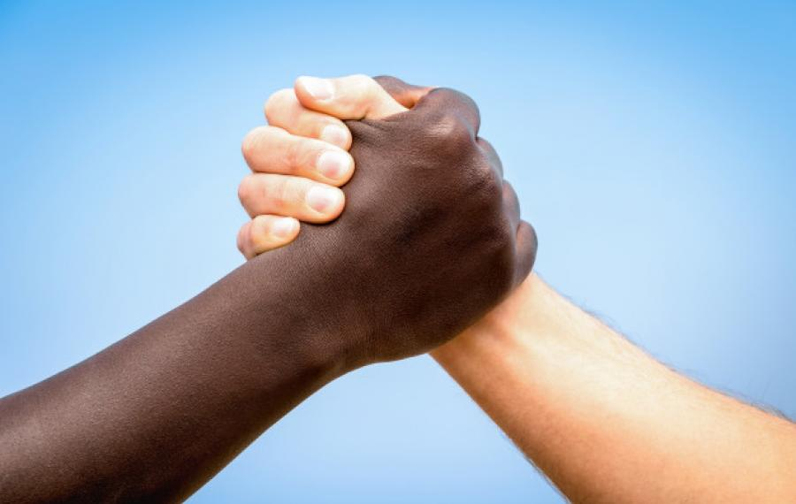 Two hands interlocking of different skin colors