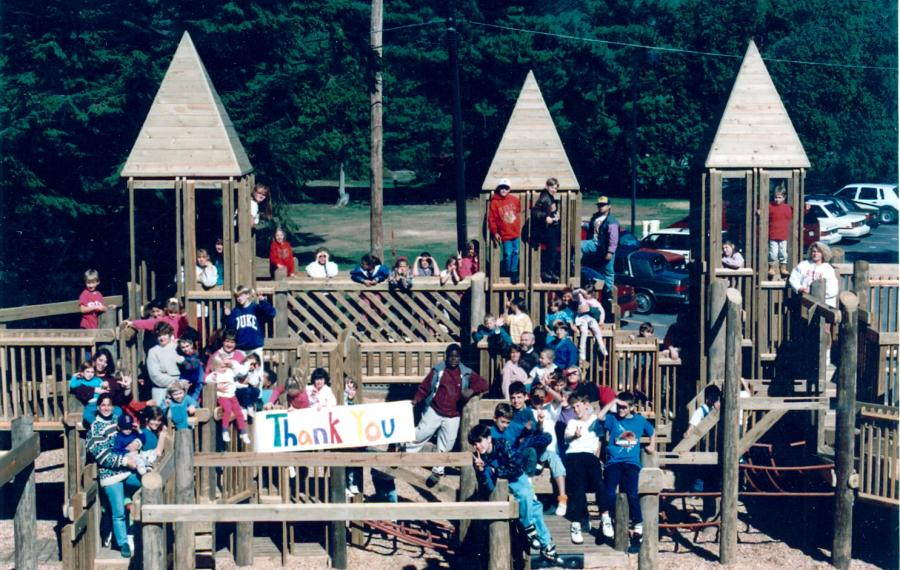 Group of students holding a sign saying thank you at the playground.