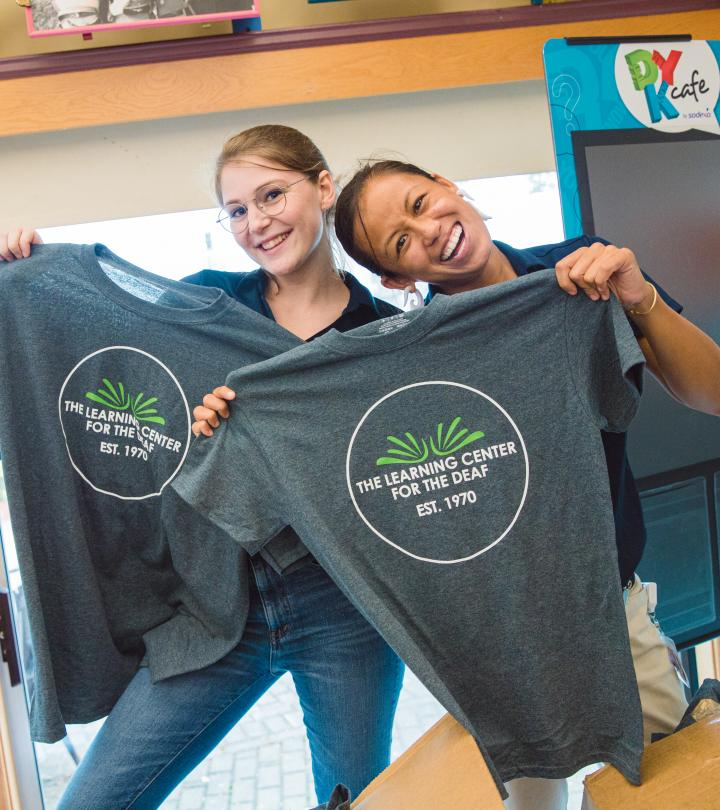 Two TLC staff smiling with TLC shirts