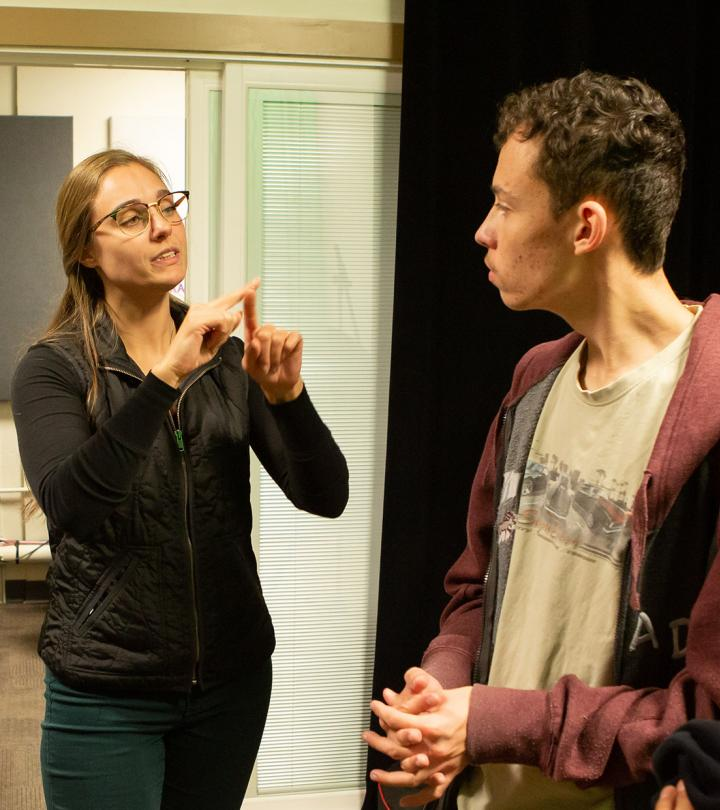 A young female on the left using American Sign Language. On the right a young male looking in her direction.