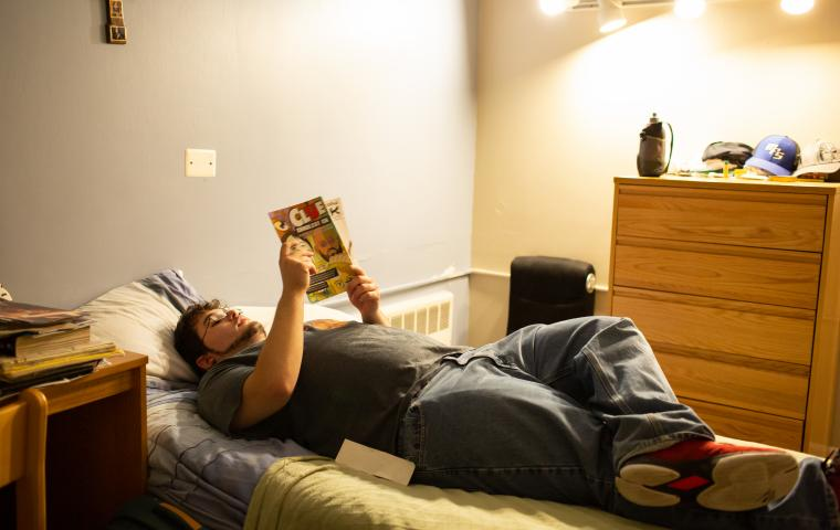 Residential student reading a book on bed.