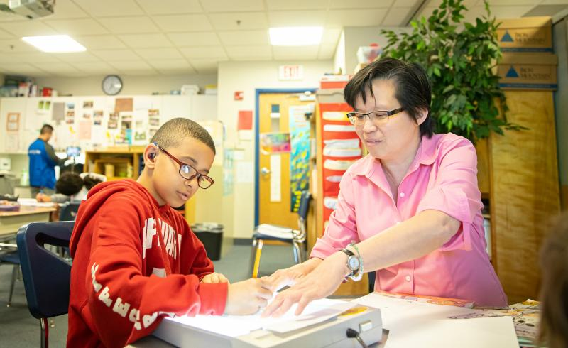 Teacher working with a student in the classroom.