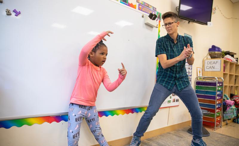 Student and teacher dancing in classroom.