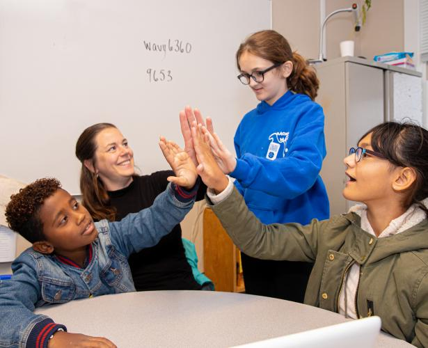 A group of students high-five each other.