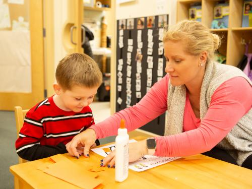 Female teacher works 1-on-1 with a young boy on an art project in a classroom.