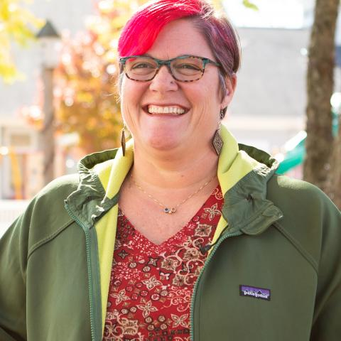 A white woman with short red hair and glasses standing outside in a green jacket.
