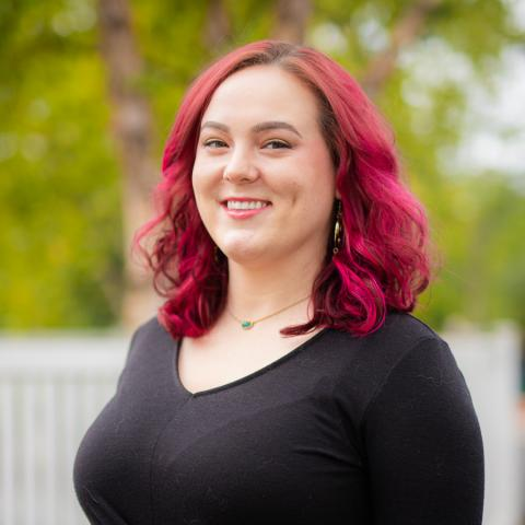 A white woman standing outside. Medium length red hair and a black long sleeved shirt.